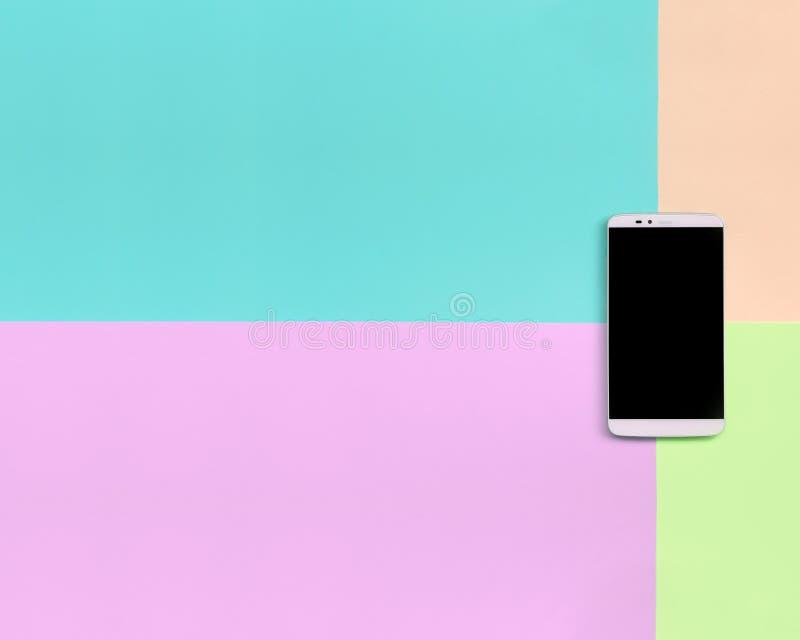 有黑屏幕的现代智能手机在时尚粉红彩笔,蓝色,珊瑚和石灰颜色纹理背景  图库摄影