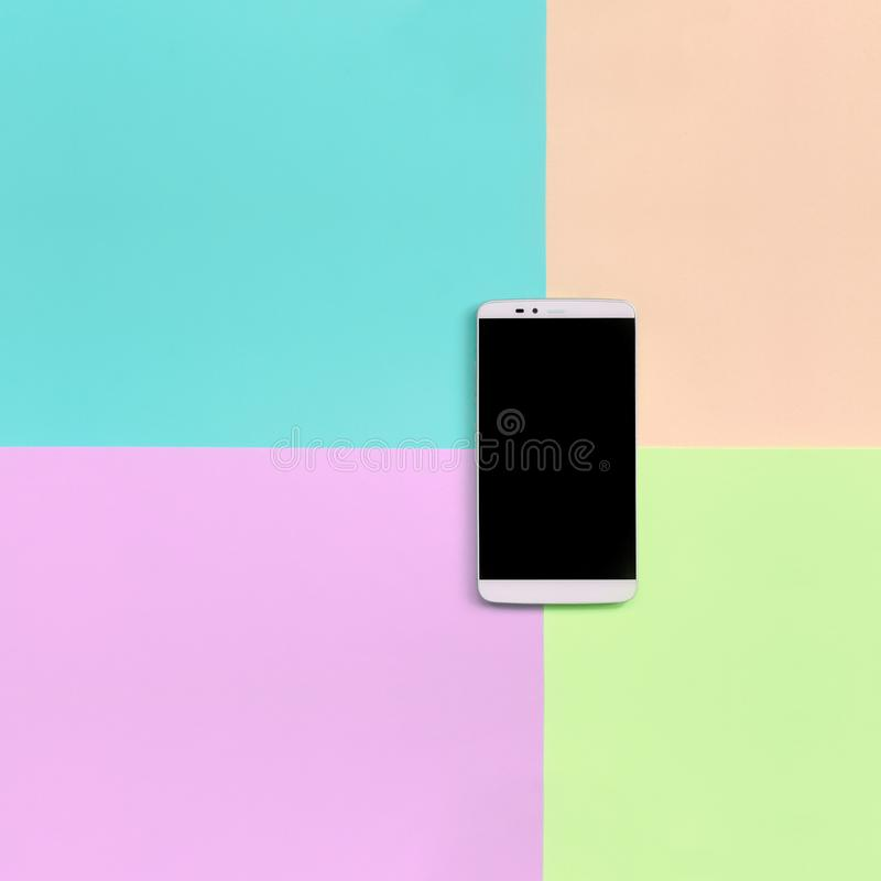有黑屏幕的现代智能手机在时尚粉红彩笔,蓝色,珊瑚和石灰颜色纹理背景  免版税库存图片
