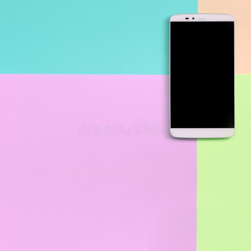 有黑屏幕的现代智能手机在时尚粉红彩笔,蓝色,珊瑚和石灰颜色纹理背景  免版税库存照片