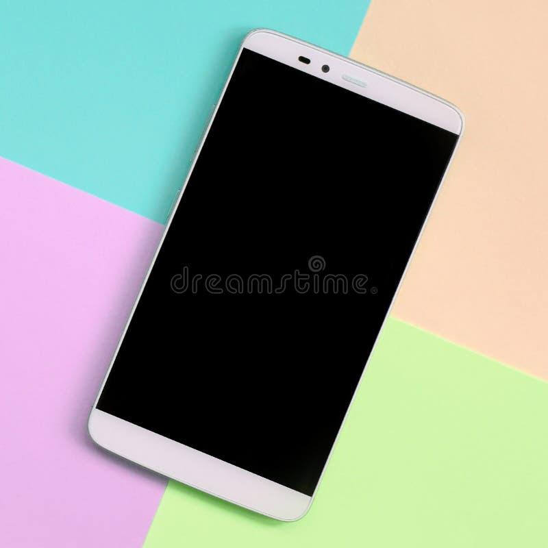 有黑屏幕的现代智能手机在时尚粉红彩笔,蓝色,珊瑚和石灰颜色纹理背景  库存照片