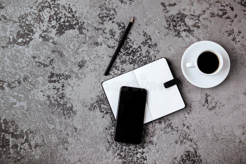 有黑屏智能手机、笔、笔记本和咖啡杯的办公桌在灰色桌上 免版税库存照片