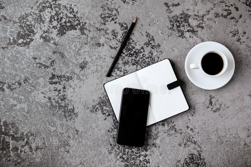 有黑屏智能手机、笔、笔记本和咖啡杯的办公桌在灰色桌上 库存图片
