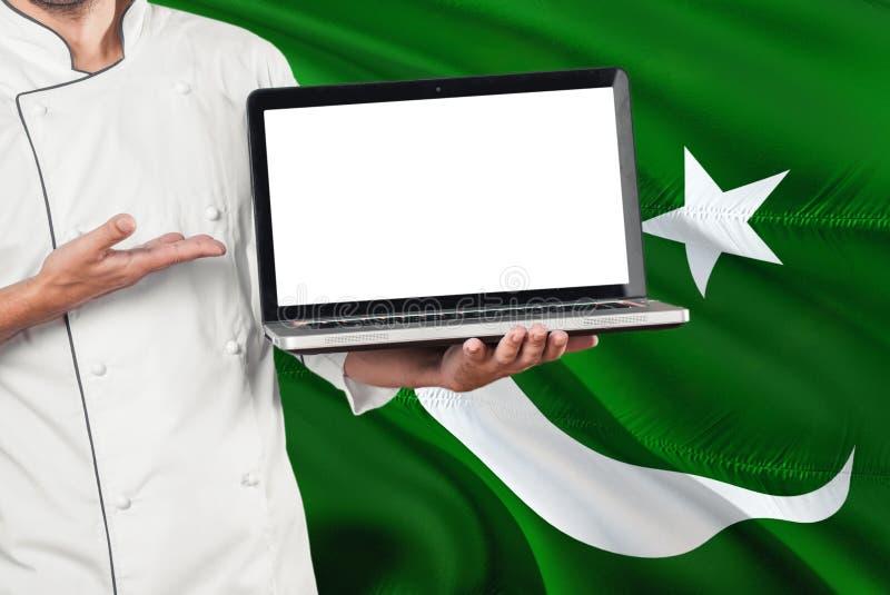 有黑屏的巴基斯坦厨师藏品膝上型计算机在巴基斯坦旗子背景 烹调佩带的制服和指向膝上型计算机拷贝的 免版税库存图片
