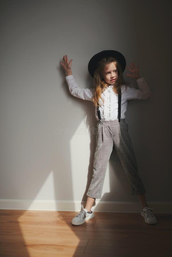 有黑帽会议的逗人喜爱的女孩在家 图库摄影