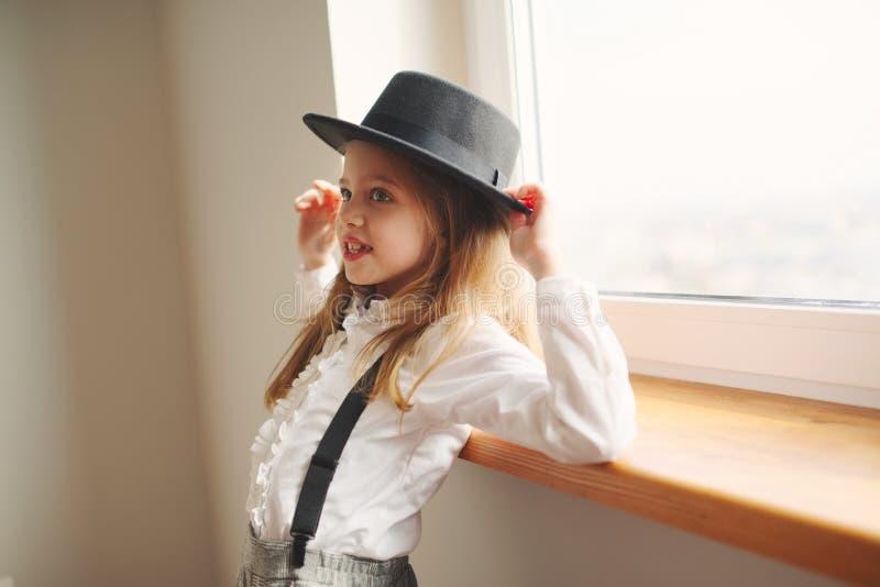 有黑帽会议的逗人喜爱的女孩在家 免版税库存照片