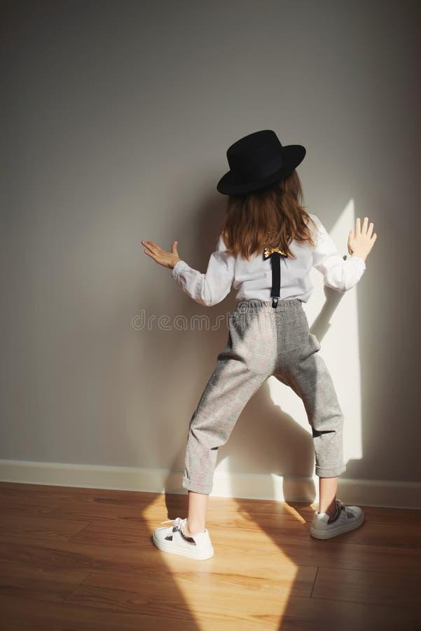 有黑帽会议的逗人喜爱的女孩在家 免版税库存图片