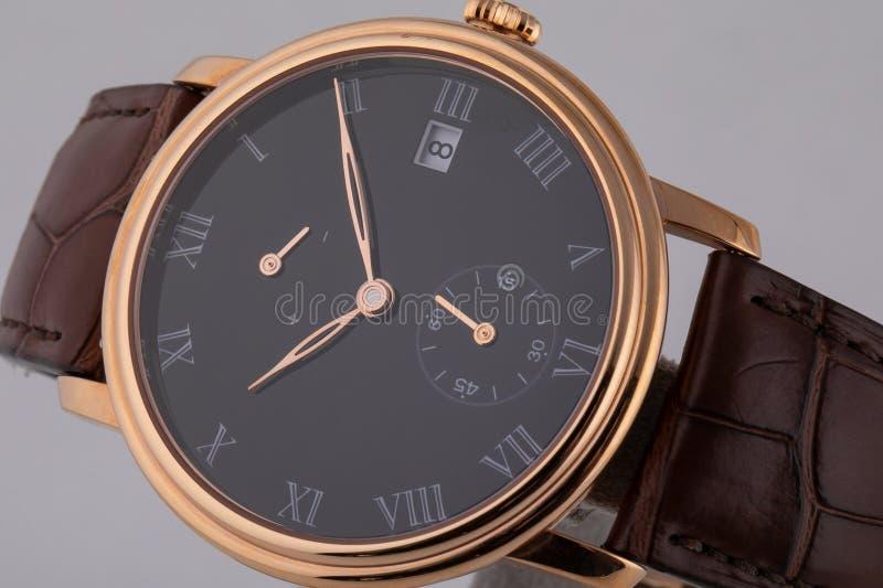 有黑拨号盘的金黄手表,金黄顺时针,秒表和测时器在白色背景隔绝的棕色皮带 免版税库存照片