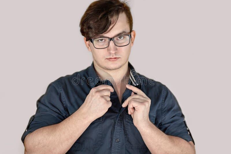 有黑暗的卷发和破裂的嘴唇的年轻英俊的白种人人,有玻璃的,解扣牛仔裤衬衣,看起来不错对加 免版税库存图片