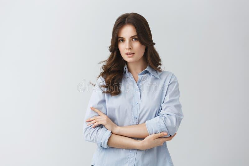 有黑暗的波浪发的嫩美丽的少妇在蓝色衬衣有严肃的神色,摆在为照片在文章 免版税图库摄影