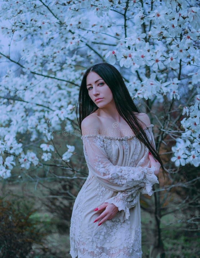 有黑暗的长发和嫉妒的逗人喜爱的可爱的夫人,站立在开花的木兰附近,穿戴令人愉快的葡萄酒 图库摄影