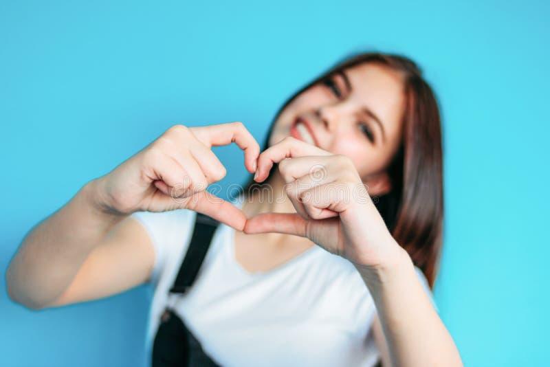 有黑暗的长发的愉快的无忧无虑的女孩在做心脏的白色T恤在蓝色背景,选择聚焦 免版税库存照片