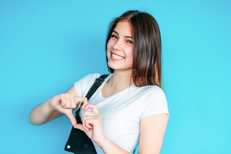有黑暗的长发的愉快的无忧无虑的女孩在做心脏的白色T恤在蓝色背景 免版税库存照片