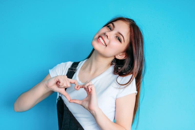 有黑暗的长发的愉快的无忧无虑的女孩在做心脏的白色T恤在蓝色背景 库存照片