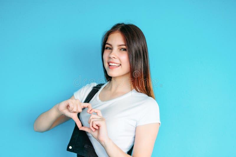 有黑暗的长发的愉快的无忧无虑的女孩在做心脏的白色T恤被隔绝在蓝色背景 免版税库存图片