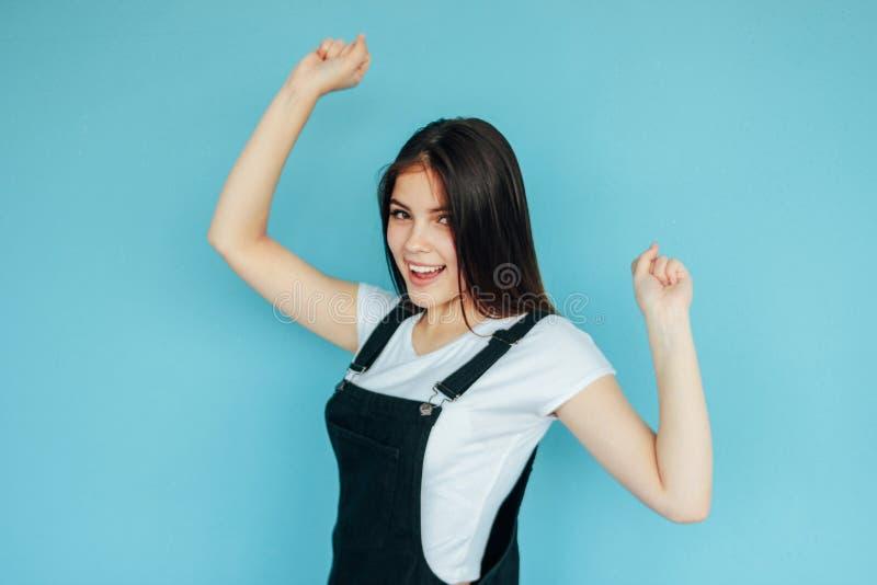 有黑暗的长发的愉快的无忧无虑的女孩在蓝色背景隔绝的白色T恤 免版税图库摄影