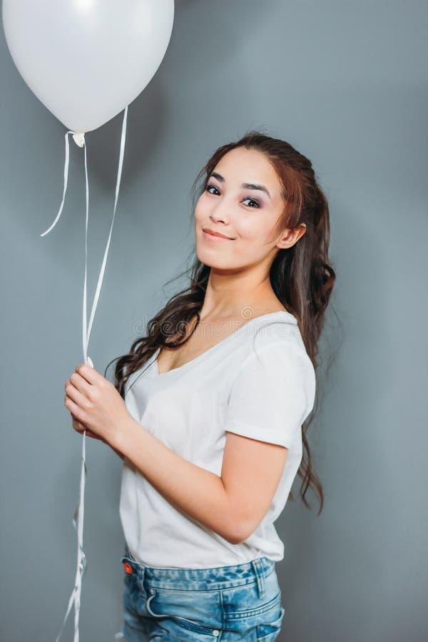 有黑暗的长发的美丽的微笑的亚裔年轻女人有在灰色背景的白色气球的 免版税库存图片