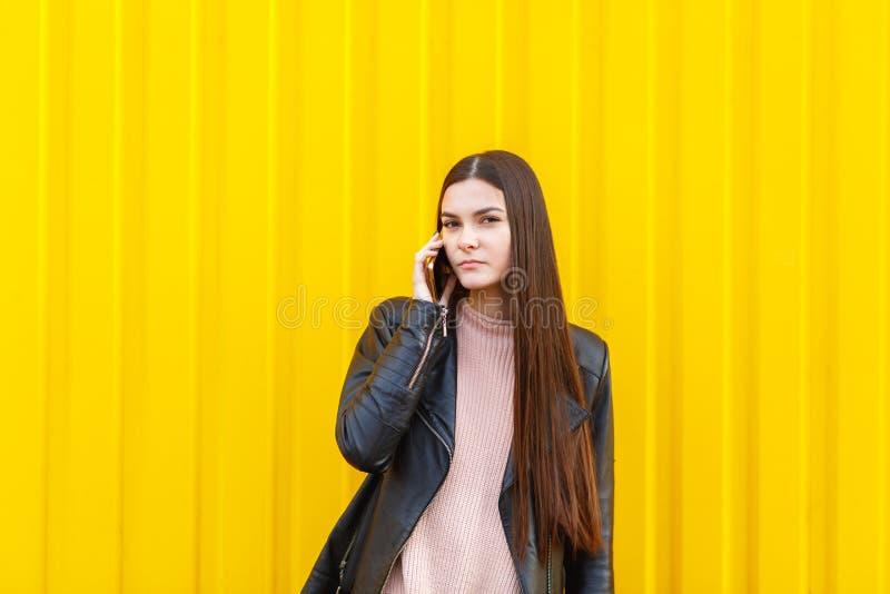 有黑暗的长的头发的一个女孩,谈话在她的手机 在一个黄色背景 库存图片