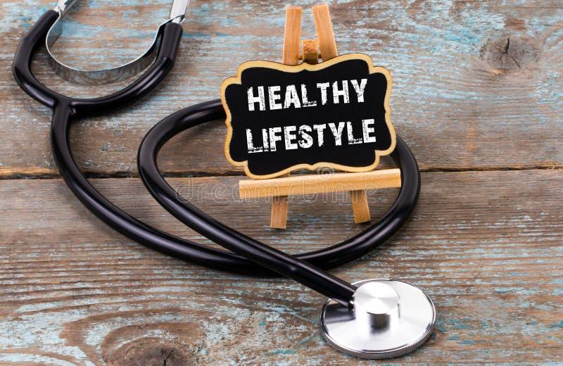 有黑板的听诊器有文本的:在木头的健康生活方式 免版税库存照片