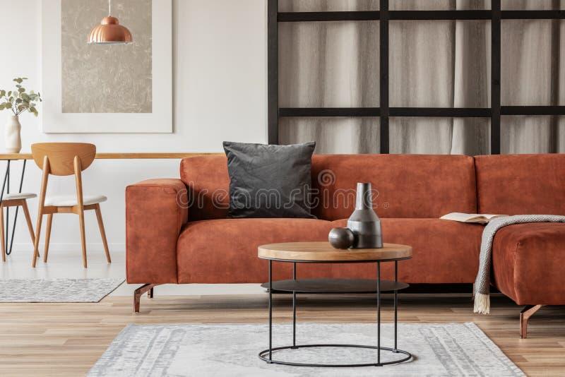 有黑枕头的时髦的壁角沙发在露天场所单室公寓 免版税库存图片