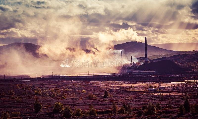 有黑烟的烟窗工厂在与云彩的天空,当日落时间、产业和污染概念 库存照片