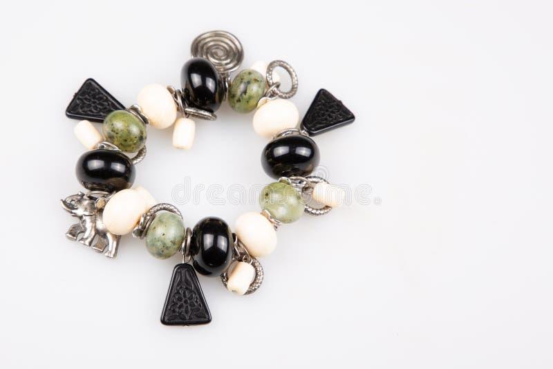 有黑白色和绿色石头球的手工制造串珠的镯子在白色背景 库存图片