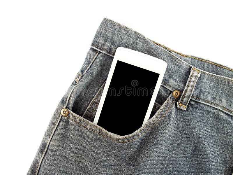 有黑空白的屏幕的白色流动智能手机在老深蓝牛仔裤前面口袋 免版税库存照片