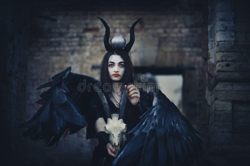 有黑翼的俏丽的邪魔女孩在她的后面后,以远另一个世界的女神,万圣节黑色天使 免版税库存图片