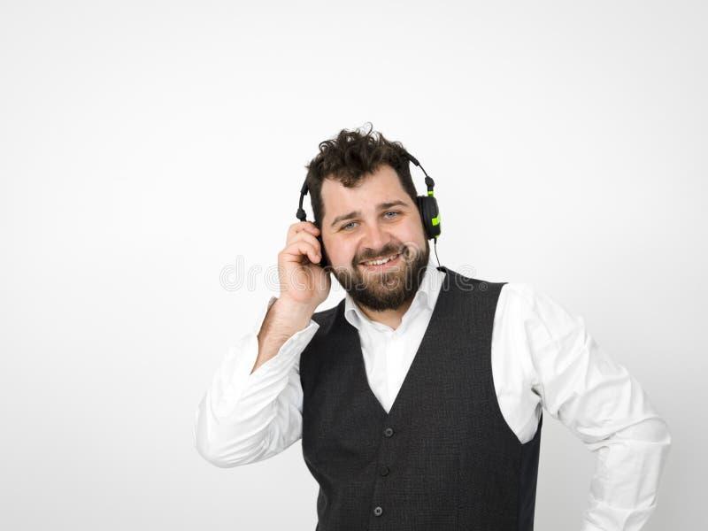 有黑胡子和白色衬衫的凉快的人摆在与耳机和智能手机在白色背景前面 免版税图库摄影