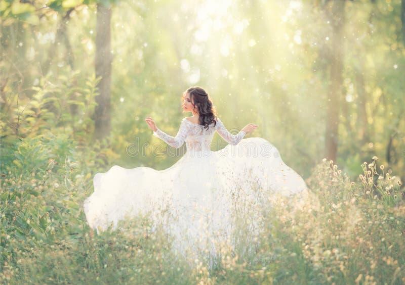 有黑色头发的典雅和嫩女孩在白色典雅的轻的礼服,夫人奔跑在森林,在照相机的转动的俏丽的面孔里 免版税图库摄影