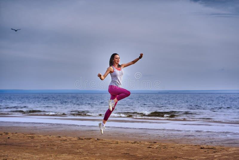 有黑色头发跃迁的年轻女人,当跑步时 免版税库存照片