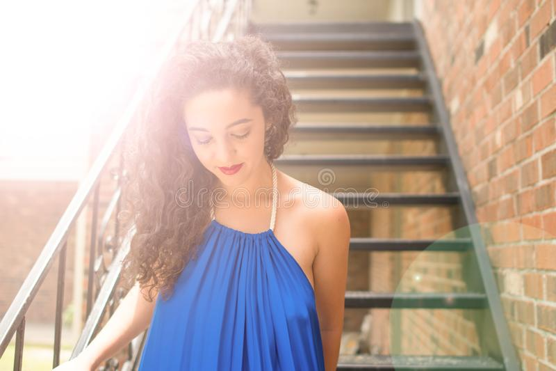 有黑褐色卷发的一美丽的年轻女人步行沿着向下阶梯步级 库存照片