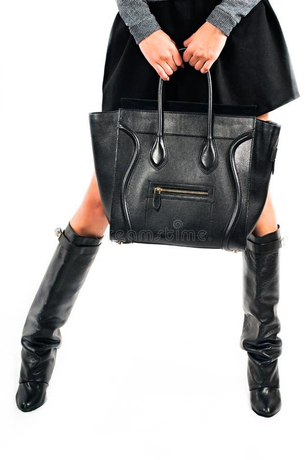 有黑起动的妇女腿和在白色背景的一个袋子 库存照片