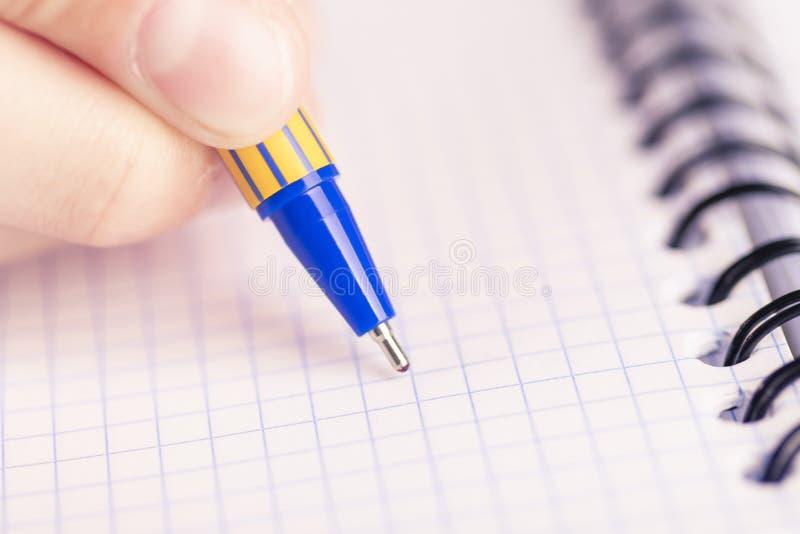有黑金子笔的人的手在方格的笔记本一床干净的床单  免版税库存照片