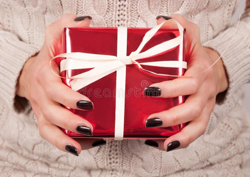 有黑钉子和毛线衣举行红色礼物盒的女孩手 免版税库存图片