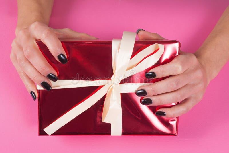 有黑钉子的女性手在有白色弓的红色礼物盒修剪在桃红色背景,关闭 免版税库存照片