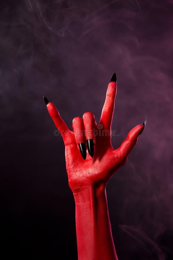 有黑锋利的钉子的红魔手 免版税库存照片