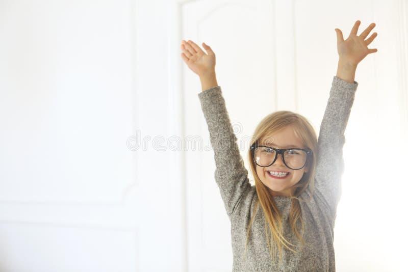 有黑镜片的微笑的逗人喜爱的女孩在白色背景 图库摄影