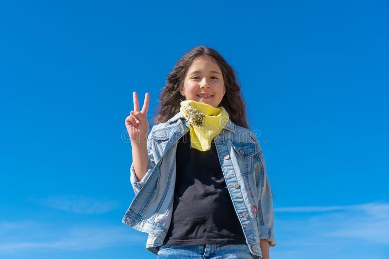 有黑长发的女孩反对清楚的天空蔚蓝微笑的看对显示手指的照相机做胜利标志 免版税库存照片