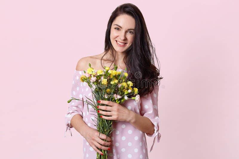 有黑长的波浪发的可爱的年轻女人,拿着花,穿戴在圆点礼服,有春天心情,摆在光 免版税库存照片