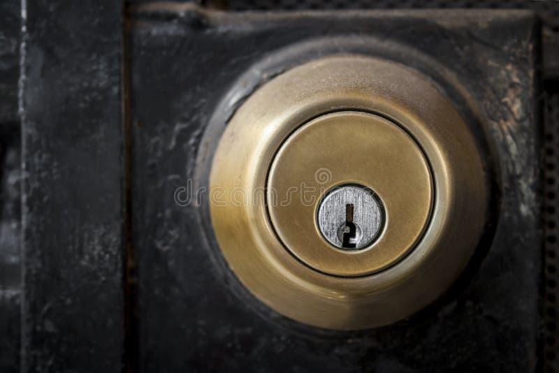 有黑门的金黄金属门锁 免版税图库摄影