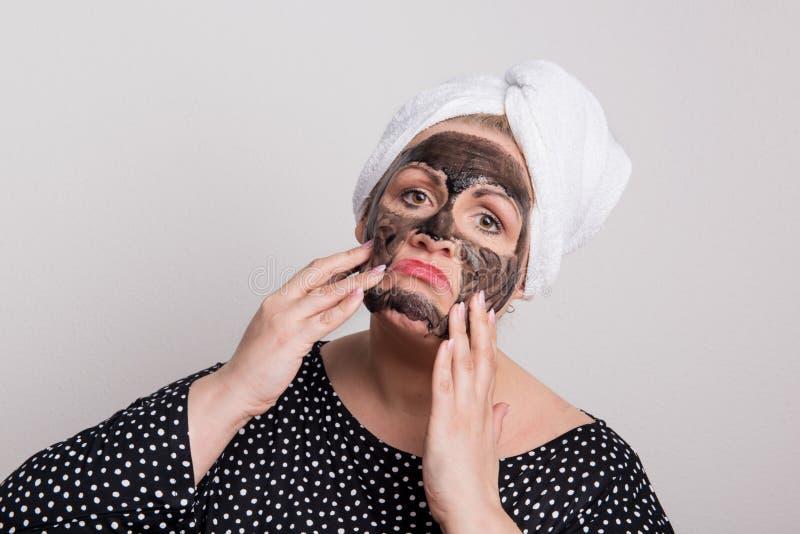 有黑面部面具的一名哀伤的超重妇女在她的面孔在演播室 库存照片