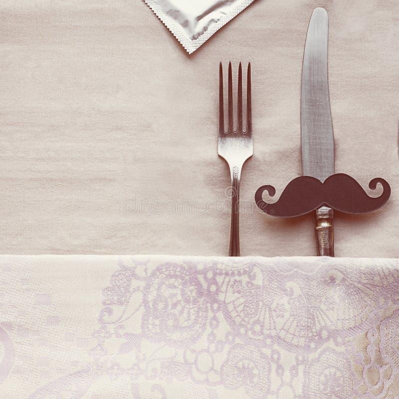 有黑髭的葡萄酒在bage桌布的刀子和叉子,作为男人和妇女床和避孕套包裹的,创造性的概念为 库存照片