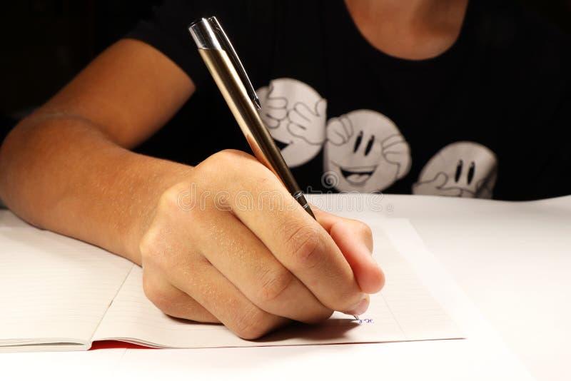 有黑T恤杉文字口述的一个年轻男孩在英国教训 男孩基本exellent女孩懒惰学习进程学校 库存图片