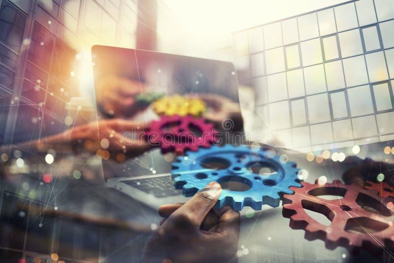 有齿轮的商人在手中从膝上型计算机的那出口 遥远的合作和配合的概念 两次曝光 库存图片