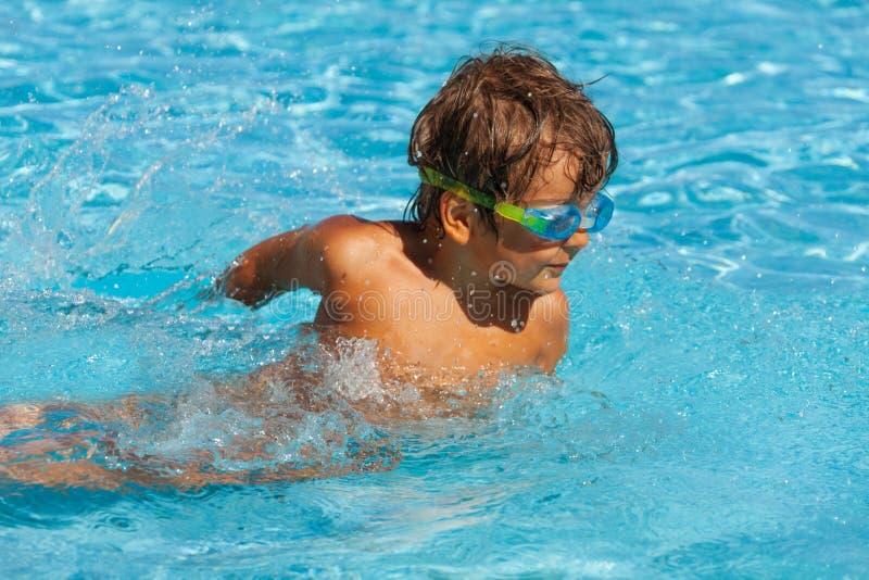 有水上运动风镜的小男孩在水池游泳 库存图片