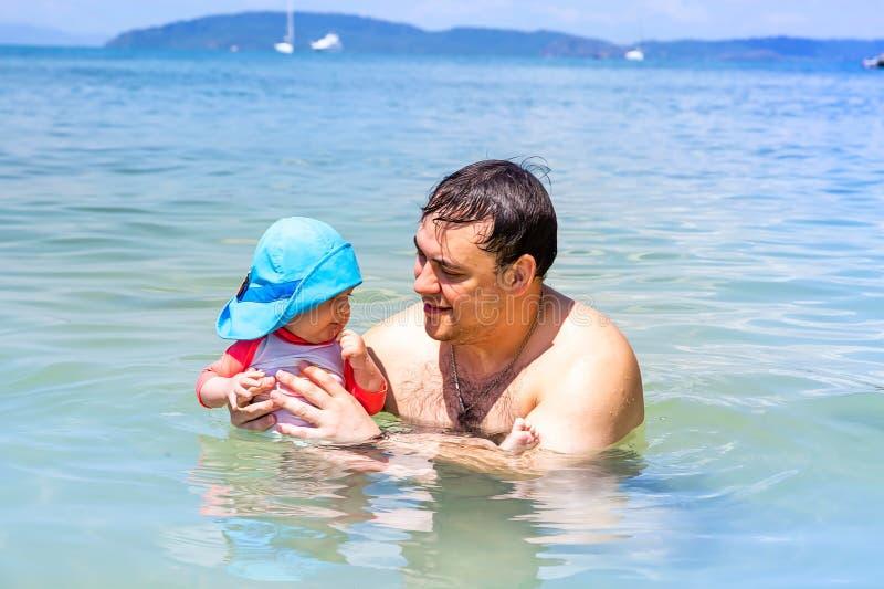 有9个月婴孩游泳的愉快的父亲在海,他们获得乐趣 游泳的爸爸教的婴儿 免版税库存图片