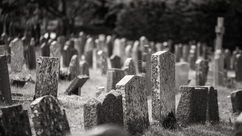 有给令人毛骨悚然的感受的老墓石的单色坟园 库存照片