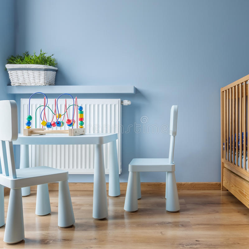 有轻便小床的蓝色婴儿室 库存图片