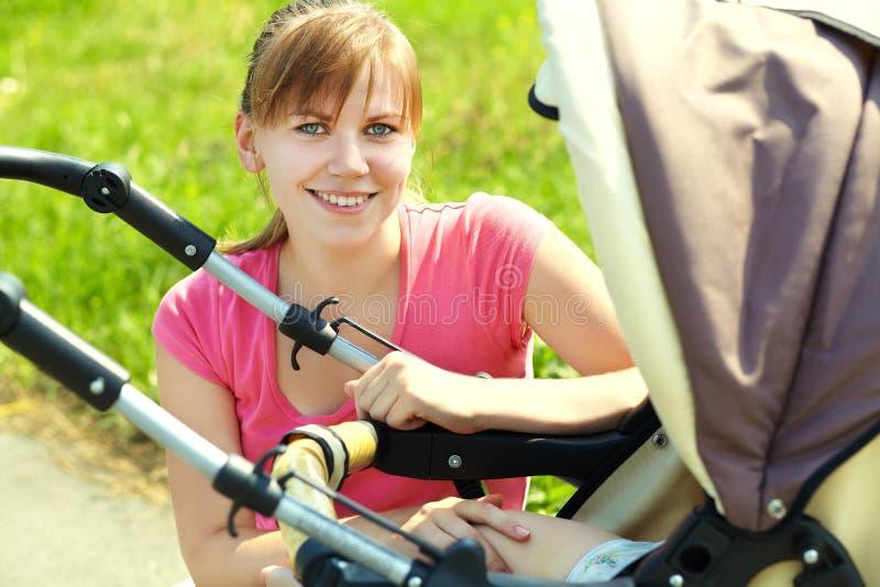 有婴儿推车的年轻母亲 库存照片