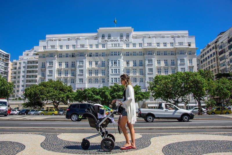 有婴儿车的年轻美丽的妇女在科帕卡巴纳宫殿背景在里约热内卢,巴西 免版税库存图片